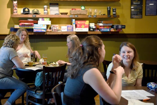 Team Alexandria Lawrence, right, discusses an answer with Sequoya Moore as Team Triple B's does the same behind them as they play Gilmore Girls trivia at The Casual Pint on May 21, 2019.