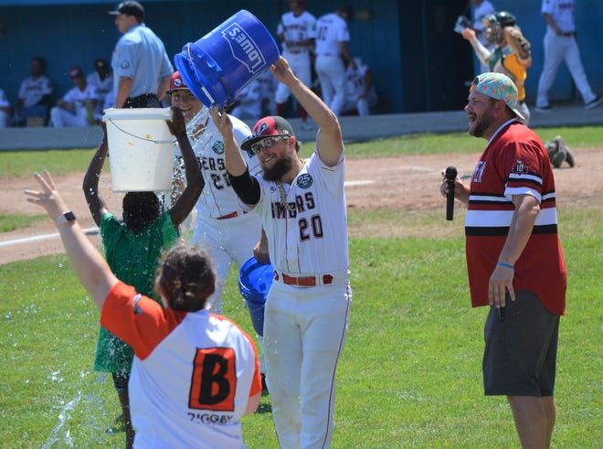 Battle Creek Bombers General Manager Tyler Shore is at the microphone during a game last season as Bombers players have fun with the fans in between innings.