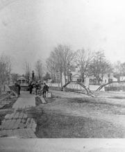 The Chenango Canal (now State Street) passes under the bridge at Lewis Street in Binghamton, about 1860.