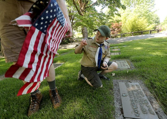 Logan Lees, 11, takes a flag from fellow Scouts BSA Troop 1541 member Erik Schroeder to place at the headstone of a veteran's grave in observance of the upcoming Memorial Day holiday, at Forest Lawn Cemetery in Bremerton, Washington, on Wednesday, May 22, 2019.