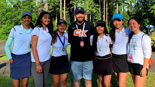 Central Kitsap senior Brittany Kwon (third from left) poses for a photo with golf coach Danny Sullivan and teammates after winning the Class 3A state golf tournament Wednesday at Hawks Prairie Golf Course in Lacey.