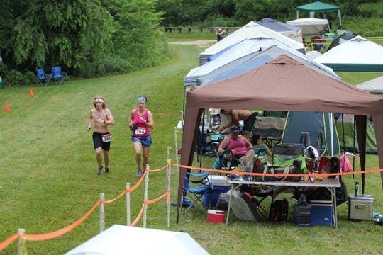 "A pair of runners in the 2018 Black Mountain Monster pass through ""tent city"" as the complete a lap in the ultramarathon, which returns on June 8."