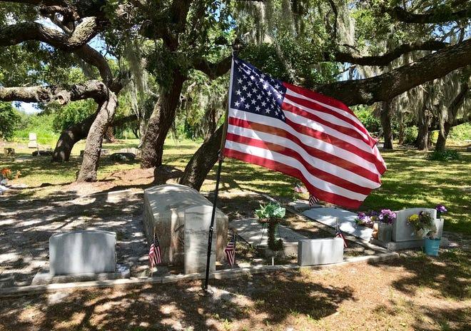 A U.S. flag flies alongside gravesites beneath an oak canopy at J.N. Tucker Memorial Cemetery in Melbourne.