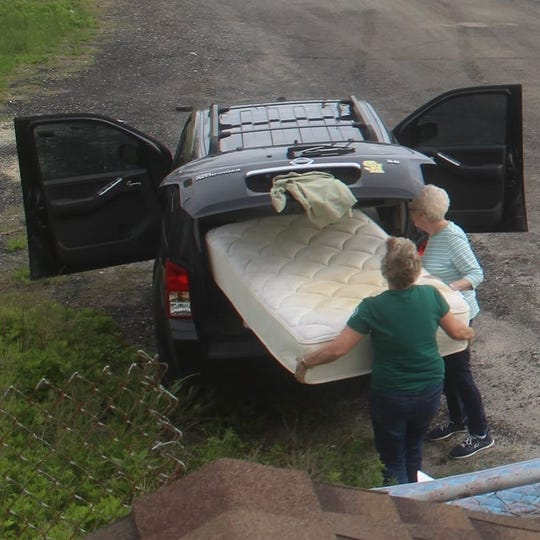 Two women pulled a stained mattress from an SUV before dumping it outside Wildwood's recycling facility.