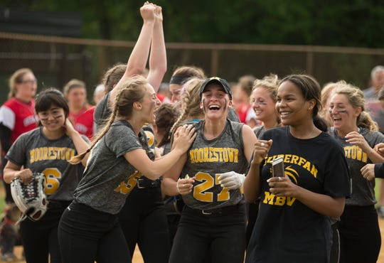 Members of the Moorestown High softball team celebrate after defeating Ocean City, 4-2, in the softball sectional semifinal playoff game played at Moorestown High School on Thursday, May 23, 2019.