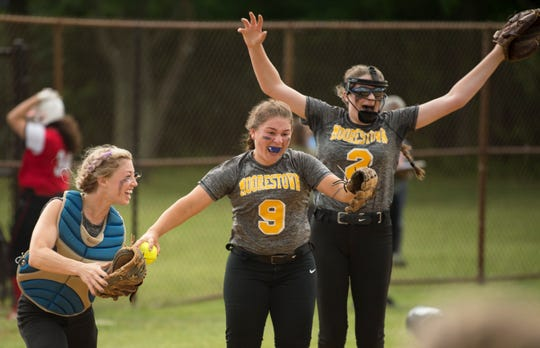 Moorestown's, from left, Claire Falcon, Sophia Gillespie, and Elysa Bohr, celebrate after the final out of the softball sectional semifinal playoff game between Moorestown and Ocean City, played at Moorestown High School on Thursday, May 23, 2019.    Moorestown defeated Ocean City, 4-2.