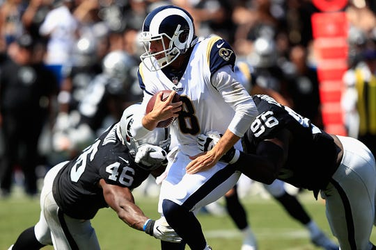 Tank Carradine #96 and Jason Cabinda #46 of the Oakland Raiders pursue Brandon Allen #8 of the Los Angeles Rams during the second half of a preseason game at Los Angeles Memorial Coliseum on August 18, 2018 in Los Angeles, California.