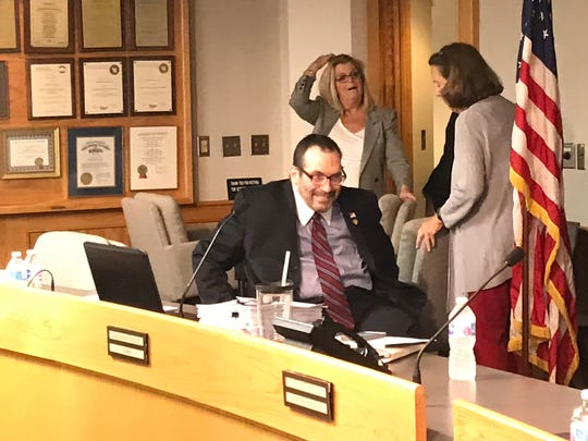 Todd Portune arrives at Thursday's Hamilton County Board of Commissioners meeting with a smile.