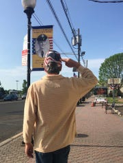 Manville Mayor Richard Onderko salutes the Hometown Hero banner of Col. John Dudash, a Manville resident who was killed in the Vietnam War. The banner is on North Main Street by the Manville Bakery.
