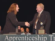 MCVTS Board of Education President Eugene J. Mullen III receives the Albert Hudanish Leadership Award from Superintendent of Schools Dianne D. Veilleux at the annual apprentice graduation in East Brunswick.