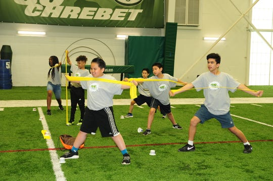 Students from Benjamin Franklin Elementary School and Herbert Hoover Middle School in Edison participated in a dairy yoga session during their trip to the New York Jets' training center in Florham Park, for an end-of-the-year Fuel Up to Play 60 event.