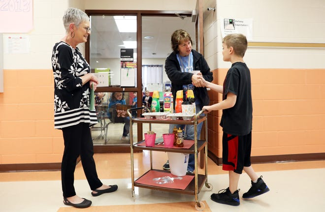 Aiden Clark gets a handshake from teacher Leslie Craft after bringing her coffee from the Coshocton Elementary School coffee cart. At left is Clark's teacher Kathleen Loughlin.