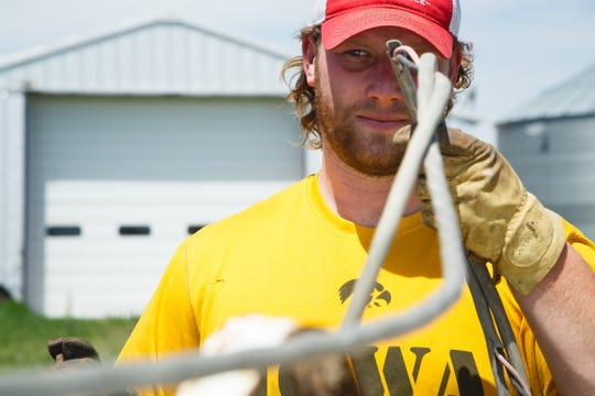 Drew Ott wrangles power cords while trying to pump fuel into his tractor.