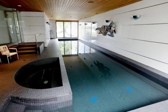 A 40-foot lap pool ends at a view of the lake. Behind the hot tub at left is the glass wall of a gym. This room has a separate dehumidifying system.