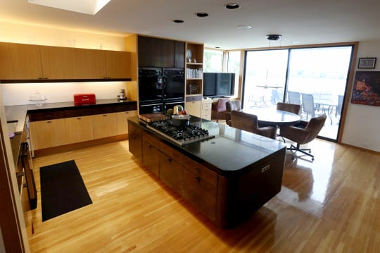 In contemporary style, the kitchen cabinets are unadorned except for their own fine wood grain. Here a light golden color is accented with deep brown wood. This room opens out to the terrace and the lake.