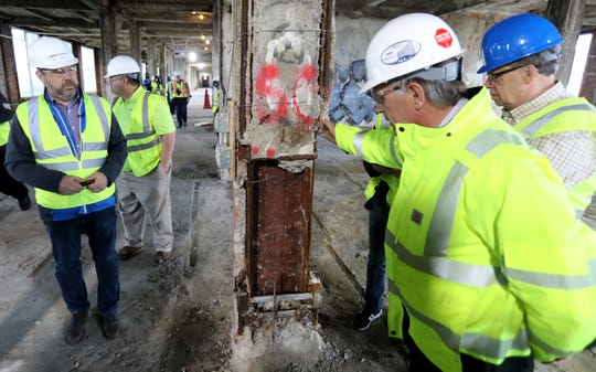 Members of the media listen to construction workers talk about the steel beams on the twelfth floor during a walk around tour at the Michigan Central Station.on Thursday, May 23, 2019.