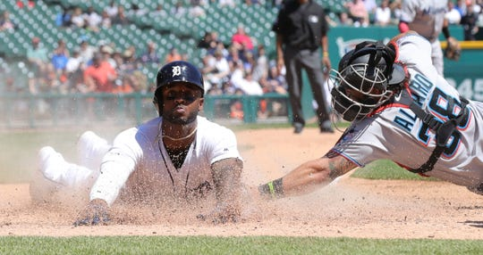 Detroit Tigers center fielder Niko Goodrum scores ahead of the tag by Miami Marlins catcher Jorge Alfaro during the sixth inning Thursday, May 23, 2019 at Comerica Park.
