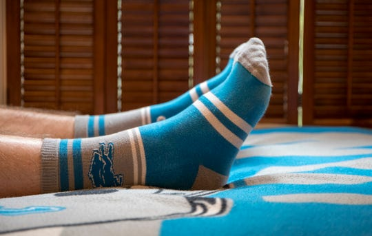 Detroit Lions Superfan Danny Ervin, 17 of Bloomfield Hills relaxes at home in his Lions socks on his Lions bedspread in Birmingham, Mich., Monday, May 20, 2019.
