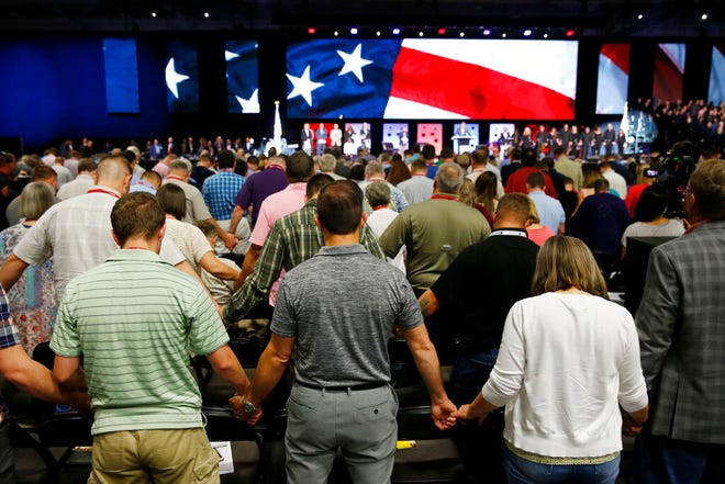In this June 12, 2018 file photo, people pray for America at the 2018 annual meeting of the Southern Baptist Convention at the Kay Bailey Hutchison Dallas Convention Center in Dallas.  The nation's largest Protestant denomination is reporting its twelfth year of declining memberships. On Thursday, May 23, 2019, the Southern Baptist Convention reported total membership for 2018 at 14.8 million, down about 192,000 from the previous year.