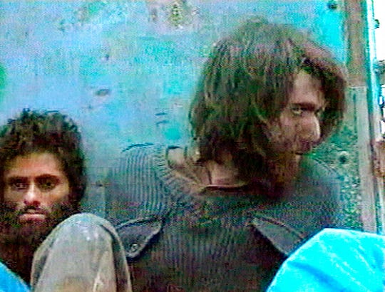 This file image taken Dec. 1, 2001, from television footage in Mazar-i-Sharif, Afghanistan, shows John Walker Lindh, right, claiming to be an American Taliban volunteer. Lindh, the young Californian who became known as the American Taliban after he was captured by U.S. forces in the invasion of Afghanistan in late 2001, is set to go free Thursday, May 23, 2019, after nearly two decades in prison.