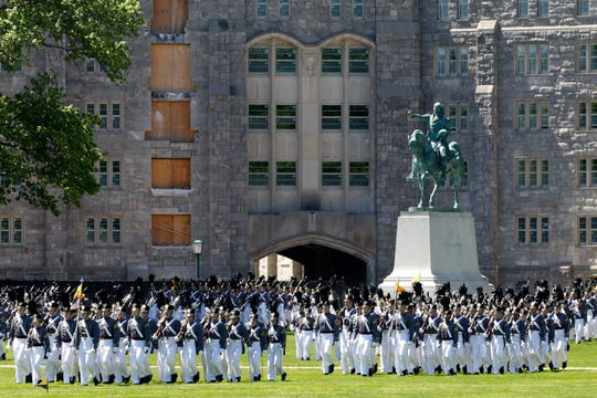 Members of the senior class march past a statue of George Washington during Parade Day at the U.S. Military Academy in West Point, N.Y.