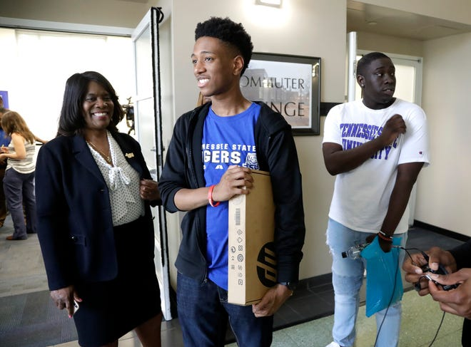 Tupac Moseley, center, leaves a news conference with a laptop computer given to him at Tennessee State University with Tennessee State President Dr. Glenda Glover, left, Thursday, May 23, 2019, in Nashville, Tenn.