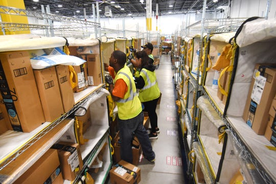 Workers move packages inside the Amazon Delivery Station as the facility gives a tour to local dignitaries and students from Romulus Middle School on Thursday, May 23, 2019.