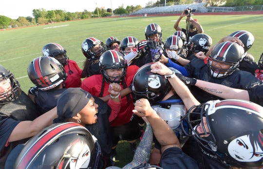 The Detroit Dark Angels fire up each other in the team huddle at the beginning of practice.