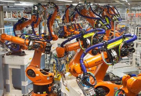 Robot arms stand at the assembly line during the reconstruction for the electrical car body construction at a press tour at the plant of the German manufacturer Volkswagen AG (VW) in Zwickau, Germany.
