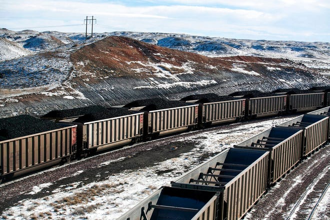 In this Jan. 9, 2014, file photo, rail cars are filled with coal and sprayed with a topper agent to suppress dust at Cloud Peak Energy's Antelope Mine north of Douglas, Wyo. Four states with climate change worries are asking a judge to stop the Trump administration from selling coal from public lands.