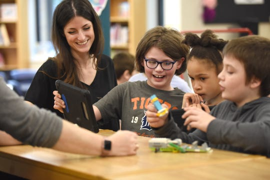 Pattengill Elementary School librarian Rachel Smith assists students Sam Dunlap, from left, Dylan Johnson and Chase Shelly on their extreme earthquake simulation project in the media center at the school in Berkley. Pattengill students will return to school before Labor Day this fall.