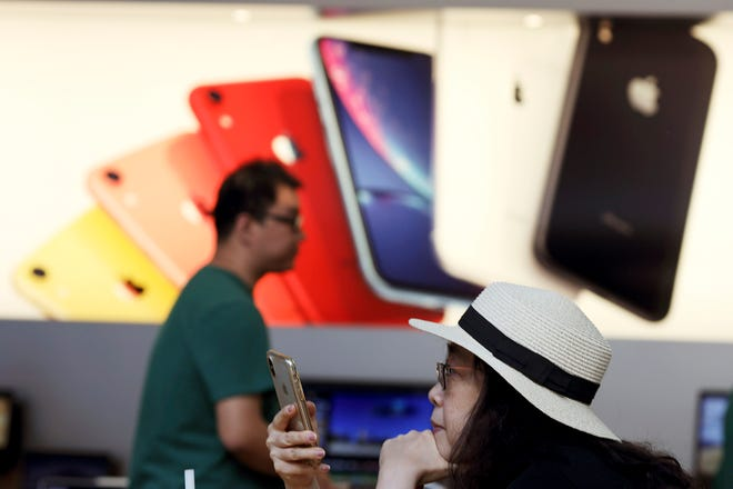 A customer looks at her iPhone at an Apple store in Beijing. Few U.S. companies are more vulnerable to a trade war with China than Apple. The company relies on factories in China to assemble the iPhones that generate most of its profits; it has also cultivated a loyal following in the country.