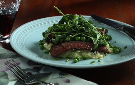 Ginger-seared skirt steak is served on a bed of grits and is topped with peas, baby lettuce and pea shoots. (Abel Uribe/Chicago Tribune/TNS)