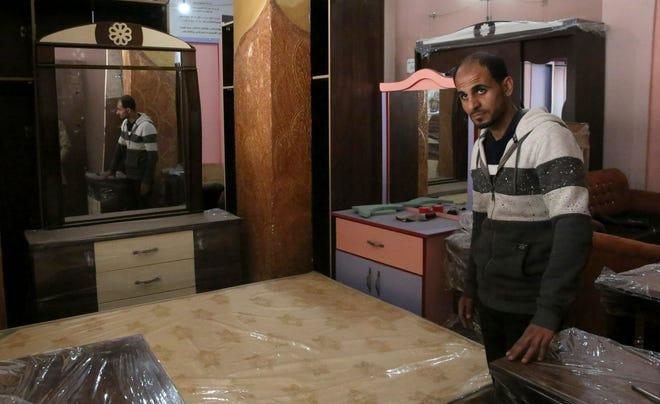 In this April 21, 2019 photo, Palestinian groom Yehiya Taleb, chooses his wedding furniture before his wedding, at a furniture workshop in Gaza City.