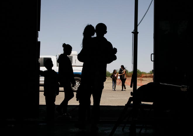 In this Wednesday, May 22, 2019 photo, migrants mainly from Central America guide their children through the entrance of a World War II-era bomber hanger in Deming, N.M.