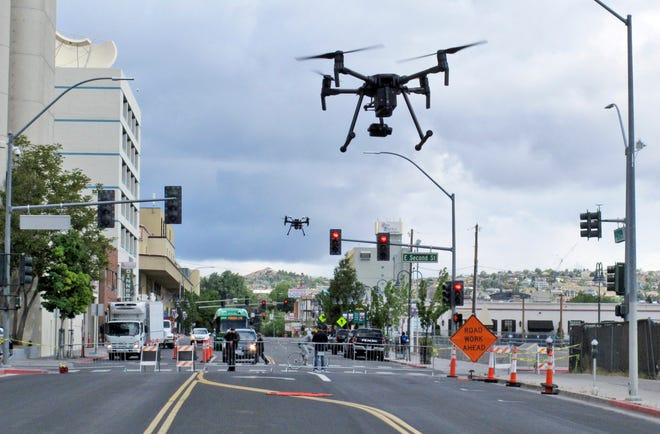 In this May 21, 2019 photo, two drones fly above Lake Street in downtown Reno, Nev.