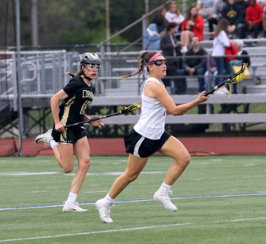 Shea Baker of Ithaca runs up the field with the ball as Corning's Charlotte Nevins gives chase during the Section 4 Class A girls lacrosse final May 22, 2019 at Ithaca High School.