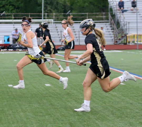 Riley Olmstead of Corning brings the ball up the field as Julia Wallace of Ithaca runs alongside her during the Section 4 Class A girls lacrosse final May 22, 2019 at Ithaca High School.