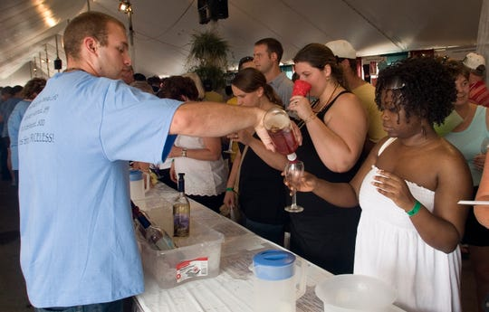 Mark Henderson of Torrey Ridge Winery pours a wine sample for Cassandre Pierre Joseph of Ithaca during the 2019 Finger Lake Wine Festival. This year's festival is canceled due to the coronavirus pandemic.
