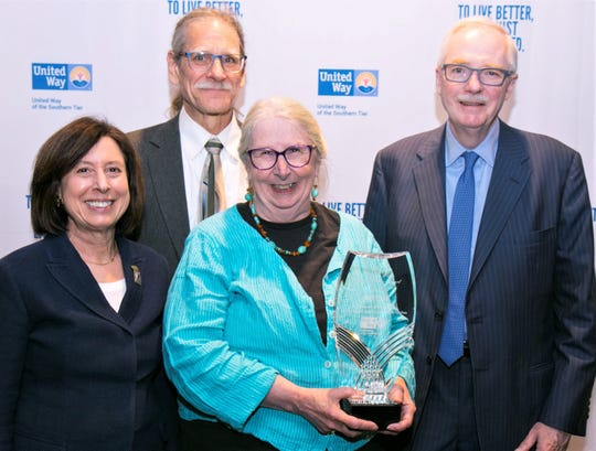 Peigi Cook, retiring executive director of the Corning Children's Center, holds the James B. Flaws Lasting Legacy Award presented to her by the United Way of the Southern Tier. Joining Cook are, from left, Marcia Weber, who presented the award, Cook's spouse Stephen Thomas, and James Flaws.