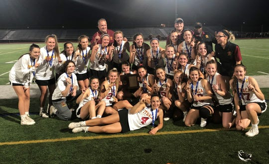 Ithaca players pose with their championship plaque after beating Corning in the Section 4 Class A girls lacrosse final May 22, 2019 at Ithaca High School.