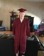 Carter Edgerley shows off his graduation gown.