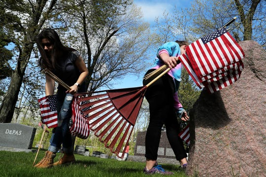 Bay View Middle School students place flags on the graves of veterans and clean up the Suamico Cemetery on Thursday, May 23, 2019 in Suamico, Wis.
