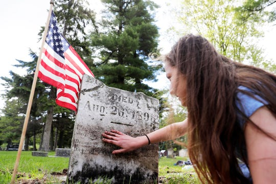 Bay View Middle School student Kailyn Kuhns reads the inscription on a 19th century gravestone while cleaning it at the Suamico Cemetery on Thursday, May 23, 2019 in Suamico, Wis. 110 Bay View students spent Thursday morning placing flags by the graves of veterans and cleaning the cemetery for Memorial Day.