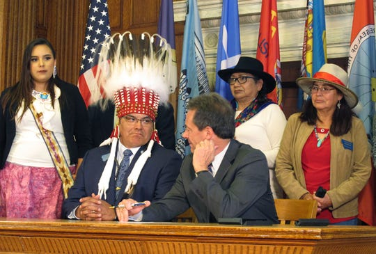Montana state Rep. Marvin Weatherwax, center left, in ceremonial headdress, speaks with Gov. Steve Bullock before a bill signing ceremony Thursday in Helena, Mont. Weatherwax sponsored legislation to install a monument and display the flags of the state's eight Native American tribes on the Capitol grounds.