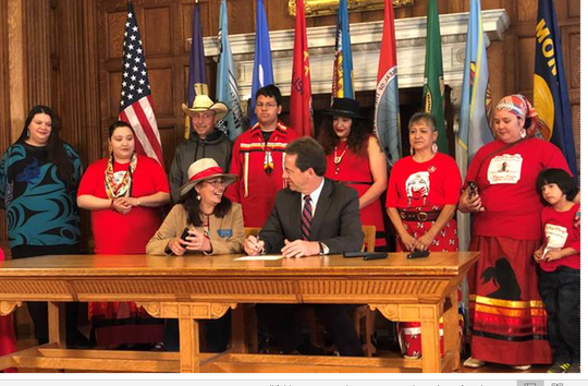 Rep. Rae Peppers, D-Lame Deer, seated left, talks with Gov. Steve Bullock during a ceremonial signing at the state Capitol in May of several bills dealing with missing persons and Native American issues.
