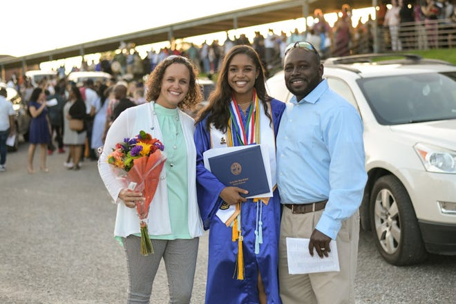 Aysha Mann and her parents Lacy Mann and Darrick Mann stand together after Aysha's graduation from North Side High School Monday.