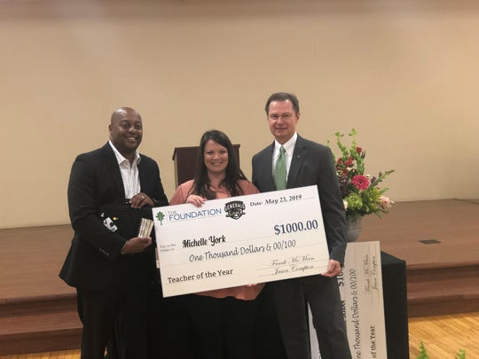 Michelle York, the 2018-19 Jackson-Madison County Schools System Teacher of the Year, accepts a $1,000 check and gifts from  Frank McMeen, president of West Tennessee Healthcare - a sponsor of the luncheon - and superintendent Dr. Eric Jones.
