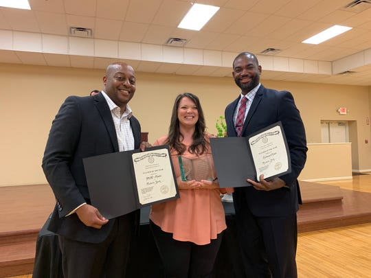Michelle York accepts her trophy and certificate for being awarded Teacher of the Year for Northeast Middle School and all middle school grades. She was later surprised to find out she also won Teacher of the Year for JMCSS. Superintendent Dr. Eric Jones and Northeast principal Michael Morris stand with her.