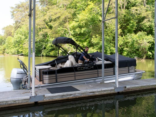Tucker Brown, a salesperson at Travis Marine, uncovers a pontoon boat housed at their Tedford Lane facilities on Wednesday, May 22, 2019.